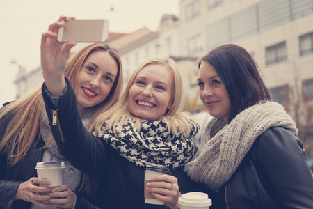 Three young adult ladies take a selfie downtown in the city center while having a coffee pause