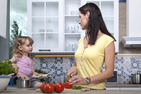 mother and toddler prepare some food in the kitchen. the look at each other while mum cuts tomatoes