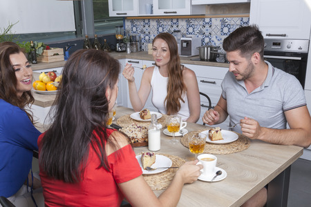 four friends enjoy crumb cake and coffee in the kitchen while discussing some gossip Banco de Imagens