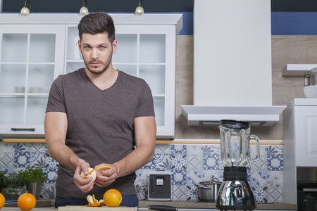 man prepares some oranges for a fruit juice at home in the kitchen.