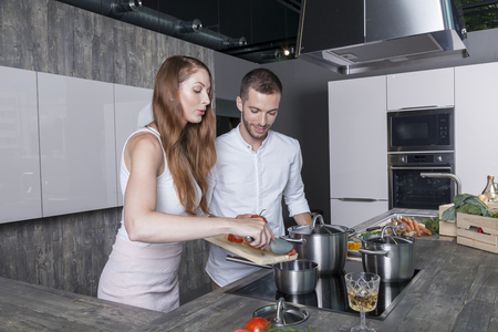 cheerful couple cooks a vegetable soup in their modern kitchen.