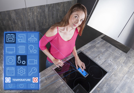 cheerful woman programs her stove with a smart kitchen app on her gadget