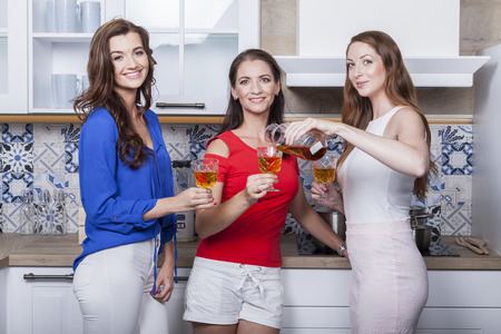 group of three friends taste moravian rose wine in the kitchen Stock Photo
