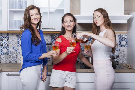 group of three friends taste moravian rose wine in the kitchen Banco de Imagens
