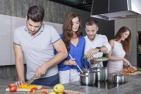 happy best friends enjoy cooking a meal together in the kitchen. they prepare an italian vegetable soup minestrone