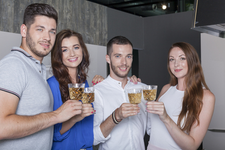 four best friends toasting with white wine enjoy the togetherness on a home party in the kitchen
