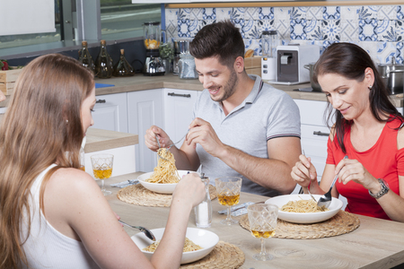 cheerful happy friends enjoy spaghetti and toasting with rose wine in the kitchen Stock Photo