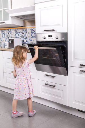 toddler girl in violet dress hot opens oven in the kitchen. she is unattended in a dangerous situation