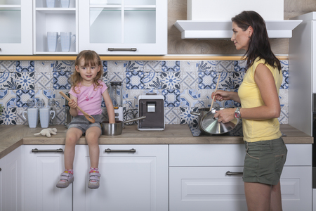 mother and toddler daughter are cooking together a meal in the kitchen Stock Photo