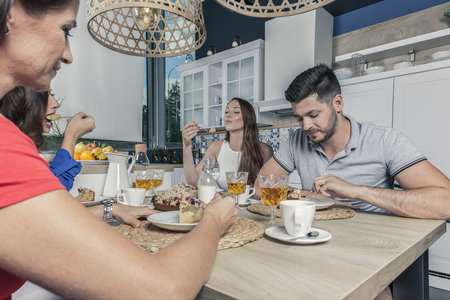 four friends enjoy crumb cake and coffee in the kitchen while discussing some gossip Stock Photo