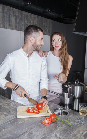 cheerful young adult people enjoy making a meal in their new kitchen Stock Photo