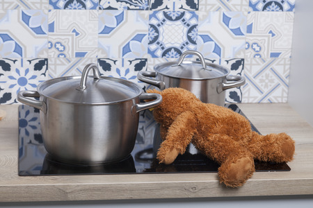 dangerous situation in the kitchen. a plush teddy bear toy lies on the stove
