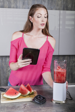 cheerful woman operates with a blender in the kitchen to prepare a fresh melon smoothie Banco de Imagens