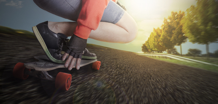 Man rides on a longboard in the street of a countryside environment with trees and blue sky