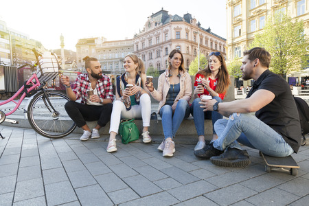 young cheerful people gathering in the city centre drinking take away coffee to go talking gossip. modern millennials communication concept