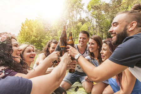 best friends toast with beer bottles and celebrate a party outdoors. Focus on the beer bottles