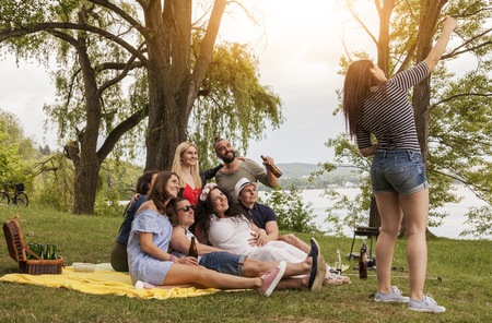 friends take a group selfie while having a picnic on a lawn next to a lake. woman takes a selfie against sunlight in summer mood