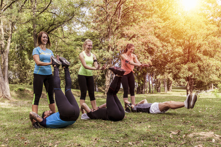 three couples sporting their exercises outdoor together. sportsmen push up their legs to train abdominal muscles similar to situps.