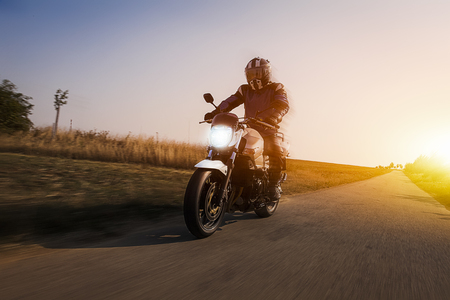motorcyclist enjoys a ride on her motorbike at sun dawn. the tarmac of the country road shows dynamic unsharpness