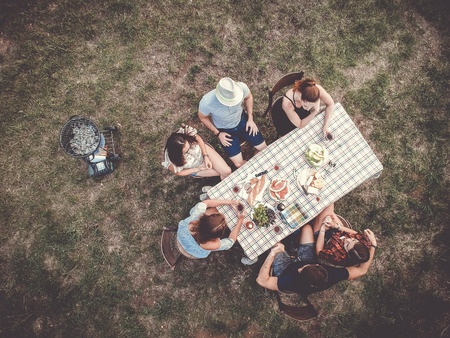 group of young people having a barbeque picnic in the garden sitting at the table drinking wine. the grill is prepared.