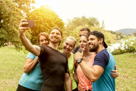 sportive friends take a group selfie in the countryside after they successfully completed a daily crossfit workout. all smile into a smart phone to then share the photo in social media