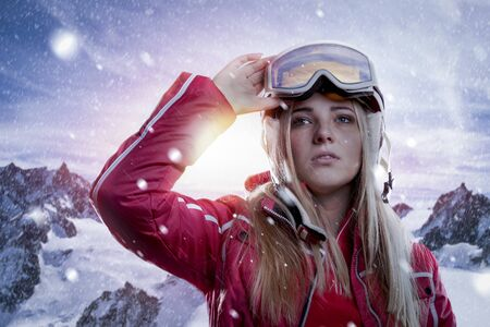 sportive young woman with helmet and goggles standing in front of mountain panorama. she enjoys landscape and infinite view to the horizon during sun dawn