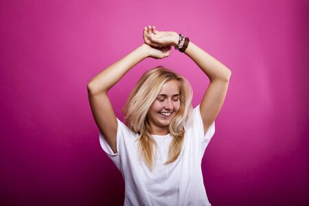 portrait of dancing blonde in white shirt in front of lilac wall
