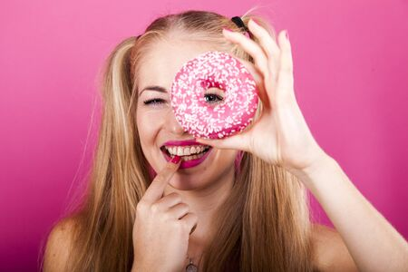 portrait of cute blond woman looking through a donut