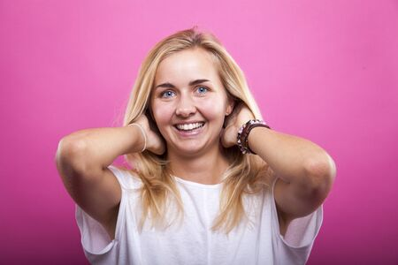 portrait of cheerful blond woman in white shirt at pink wall