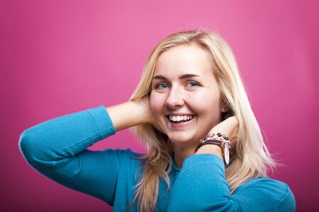 portrait of blond woman in teal sweater in front of pink wall