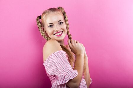 cute blonde lady with plaid pigtails leaning against pink wall