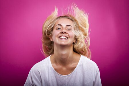 blond woman in white shirt against pink background jumping Banco de Imagens