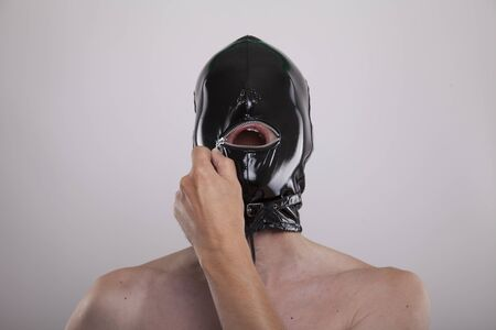submissive man opens zip of his shiny black latex mask Banco de Imagens