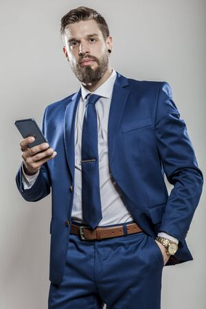 top manager in blue business suit with mobile phone standing Banco de Imagens