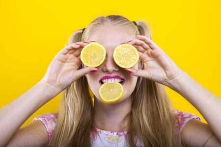 portrait of teenager with lemon slices on eyes and in mouth