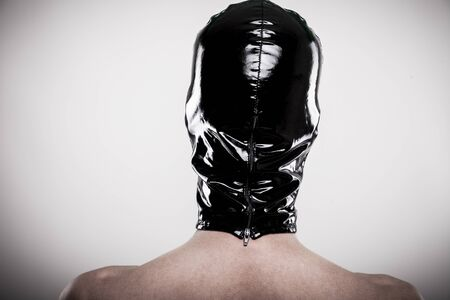 man wears shiny black latex mask with backside zipper closure, capture from behind Banco de Imagens