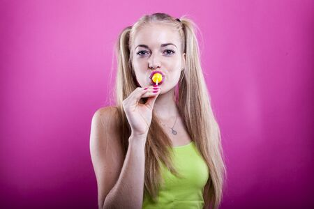 cute blonde with ponytails sucks a yellow lollipop Banco de Imagens