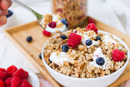 healthy oat flakes muesli with curd and berries standing on a wooden tray in daylight mood Stock Photo