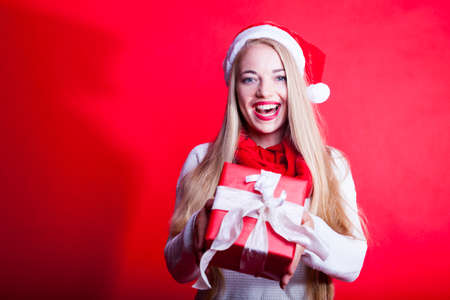 cheerful young woman in a christmas mood with santa hat and knitted sweaters and xmas presents