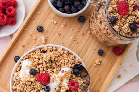 healthy breakfast with oat flakes musli and yogurt curd combined with fresh raspberries and blueberries berries served on a bamboo tray early in the morning of a sunny day Stock Photo