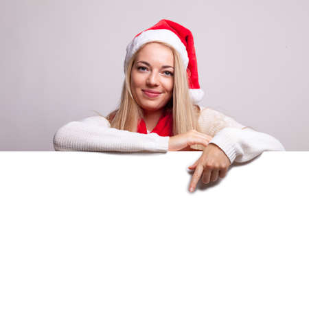 christmas woman with santa claus hat and white blank board copy space for an advertisement text.