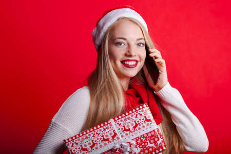 beautiful blonde with santa hat and christmas present calls someone on the phone