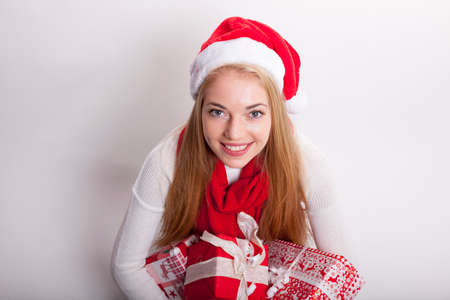 happy smiling blond woman with santa hat sitting on the floor with a load of christmas presents in her hands