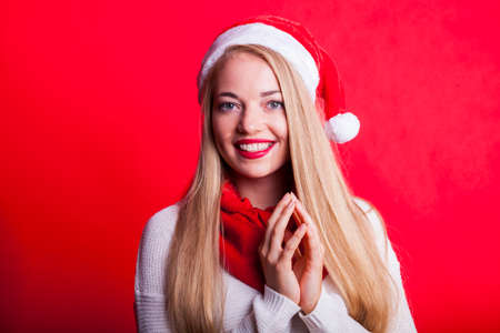 portrait of an excited blond lady in christmas mood with santa hat and folded hands