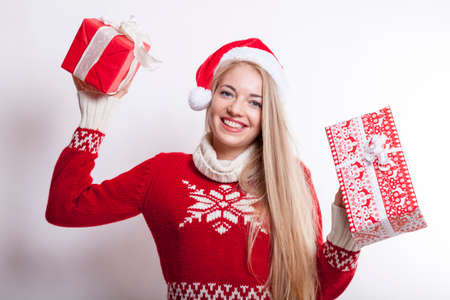 happy smiling millennial santa claus lady with jelly bag hat holds two christmas presents in her hands while standing isolated against white background