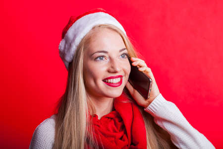 happy smiling blonde with santa hat takes a call with her smartphone.