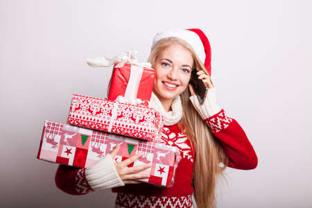 blond woman in christmas mood with santa hat and a stack of presents calling someone and smiling into the camera