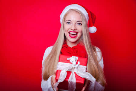 cheerful blond lady with santa hat and christmas present smiling and standing in front of red background Stock Photo