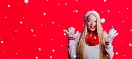 cute blonde woman with santa hat and knitwear stands in front of red background and makes an excited facial expression while gesturing with her hands. Stock Photo