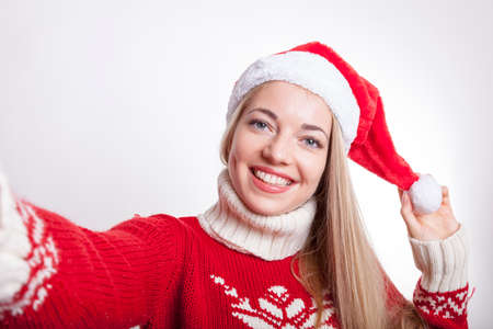 blond woman in christmas mood wearing santa hat